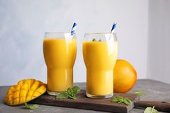 Glasses of fresh mango drink and fruits. On table royalty free stock photography