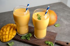 Glasses of fresh mango drink and fruits. On table stock images