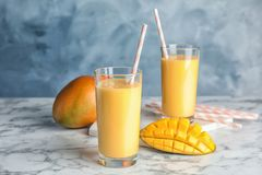 Glasses of fresh mango drink and fruits on table. Against color background stock photos