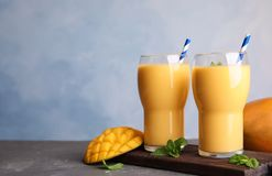 Glasses of fresh mango drink and fruits on table. Space for text royalty free stock photos