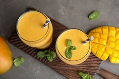 Glasses of fresh mango drink and fruits on table. Top view royalty free stock image