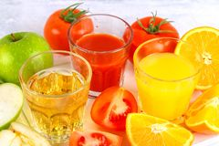 Glasses with fresh orange, apple, tomato juice on a gray concrete table. Lobules Fruits and vegetables around. Glasses with fresh orange, apple, tomato juice on stock photo
