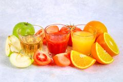 Glasses with fresh orange, apple, tomato juice on a gray concrete table. Lobules Fruits and vegetables around. Glasses with fresh orange, apple, tomato juice on stock photography
