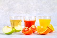 Glasses with fresh orange, apple, tomato juice on a gray concrete table. Lobules Fruits and vegetables around. Glasses with fresh orange, apple, tomato juice on royalty free stock photography