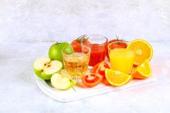 Glasses with fresh orange, apple, tomato juice on a gray concrete table. Lobules Fruits and vegetables around. Glasses with fresh orange, apple, tomato juice on stock image