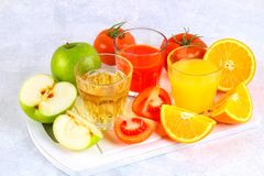Glasses with fresh orange, apple, tomato juice on a gray concrete table. Lobules Fruits and vegetables around. Glasses with fresh orange, apple, tomato juice on royalty free stock photo