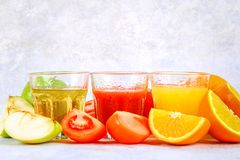 Glasses with fresh orange, apple, tomato juice on a gray concrete table. Lobules Fruits and vegetables around. Glasses with fresh orange, apple, tomato juice on royalty free stock photos