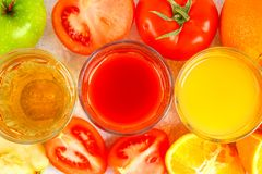 Glasses with fresh orange, apple, tomato juice on a gray concrete table. Lobules Fruits and vegetables around. Top view. Glasses with fresh orange, apple royalty free stock photography