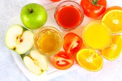 Glasses with fresh orange, apple, tomato juice on a gray concrete table. Lobules Fruits and vegetables around. Top view. Glasses with fresh orange, apple stock images