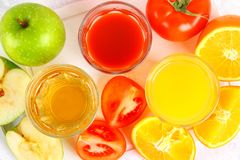 Glasses with fresh orange, apple, tomato juice on a gray concrete table. Lobules Fruits and vegetables around. Top view. Glasses with fresh orange, apple stock photo