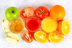 Glasses with fresh orange, apple, tomato juice on a gray concrete table. Lobules Fruits and vegetables around. Top view. Glasses with fresh orange, apple royalty free stock images