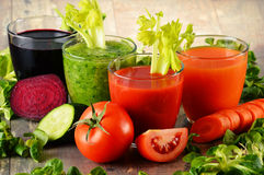 Glasses with fresh organic vegetable juices on wooden table Royalty Free Stock Images