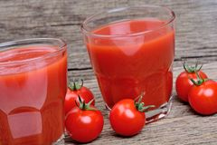 Glasses of fresh tomato juice on table Stock Photos