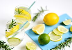 Glasses with Fresh Water Rosemary Lemon Lime Fruits Royalty Free Stock Images