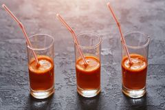 Glasses with freshly squeezed carrot juice on a dark stone backg. Round Stock Image
