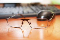 Glasses on front of keyboard and mouse Royalty Free Stock Photos