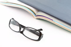 Glasses in front of opened magazines Royalty Free Stock Image
