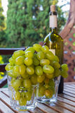 Glasses full of grapes and a bottle of wine. Two glasses full of green grapes with a bottle of Crimean wine with blurry background Stock Images
