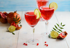 Glasses of garnet juice with lime. On white wooden background Royalty Free Stock Photos