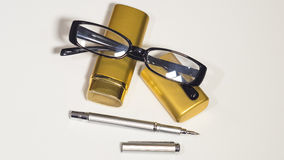 Glasses, gold case and a pen. Isolate white background. Royalty Free Stock Photo