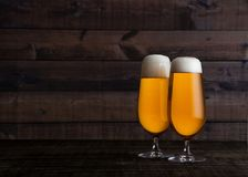 Glasses of golden lager ale beer with foam on wood. Glasses and bottle of golden lager beer with foam on wooden table background royalty free stock photos