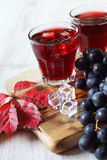 Glasses of grape juice and black grapes Stock Photography
