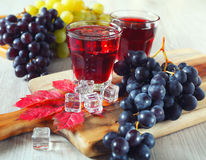 Glasses of grape juice and black and green grapes. Two glasses of grape juice with ice and black and green grapes. Toned image stock photography