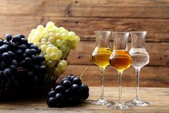 Glasses of grappa on rustic table. Background stock photos