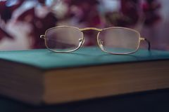 Glasses on green book. Reading concept. Closeup of spectacles on gradient background with reverberation. Selective focus royalty free stock image