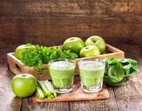 Glasses of green juice with apple, celery and spinach Stock Image