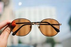 Glasses on hand. Orange glasses on hand wallpaper Stock Images