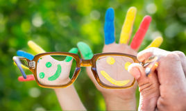 Glasses. In hand. Smiley on hands against green spring background stock photo