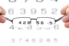 Glasses In Hands And Eye Test Chart Royalty Free Stock Photography