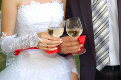 Glasses in the hands of groom and fiancee. Two glasses with champagne in the hands of groom and fiancee Stock Images