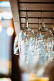 Glasses hanging above bar rack. Stock Photography