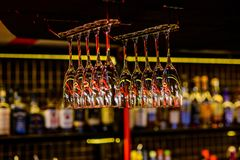 Glasses hanging above the bar in the restaurant. Glasses for alcoholic beverages. Glasses hanging above the bar in the restaurant. The empty glasses. The glasses royalty free stock images