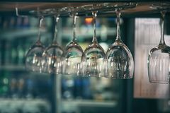 Glasses hanging on bar counte Royalty Free Stock Photos