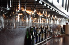 Glasses hanging at bar. A restaurant bar with glasses hanging upside down royalty free stock image