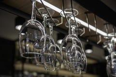 Glasses hanging over a bar rack. Wine glasses hanging over a bar rack Stock Photos