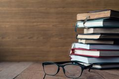 Glasses with hardback books on wooden table. Free space for text stock image