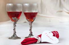 Glasses and heart. Two beautiful glasses with red napkin, heart and rose Stock Image