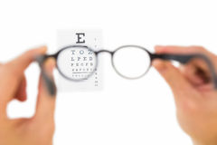 Glasses held up to read eye test Royalty Free Stock Image