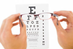 Glasses held up to read eye test Royalty Free Stock Photography