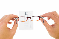 Glasses held up to read eye test Stock Photos