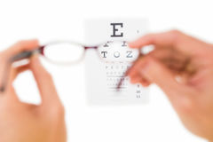 Glasses held up to read eye test Stock Images
