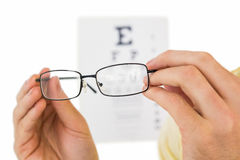 Glasses held up to read eye test Stock Image