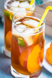 Glasses with homemade ice tea, peach flavored. Freshly cut peach slices for arrangement. Light blue wood background. Royalty Free Stock Photography