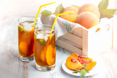 Glasses with homemade ice tea, peach flavored. Freshly cut peach slices for arrangement. White crate full with peaches in the back Stock Photography