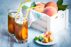 Glasses with homemade ice tea, peach flavored. Freshly cut peach slices for arrangement. White crate full with peaches in the back Royalty Free Stock Photos