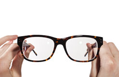 Glasses with horn-rimmed in human hands Royalty Free Stock Photography